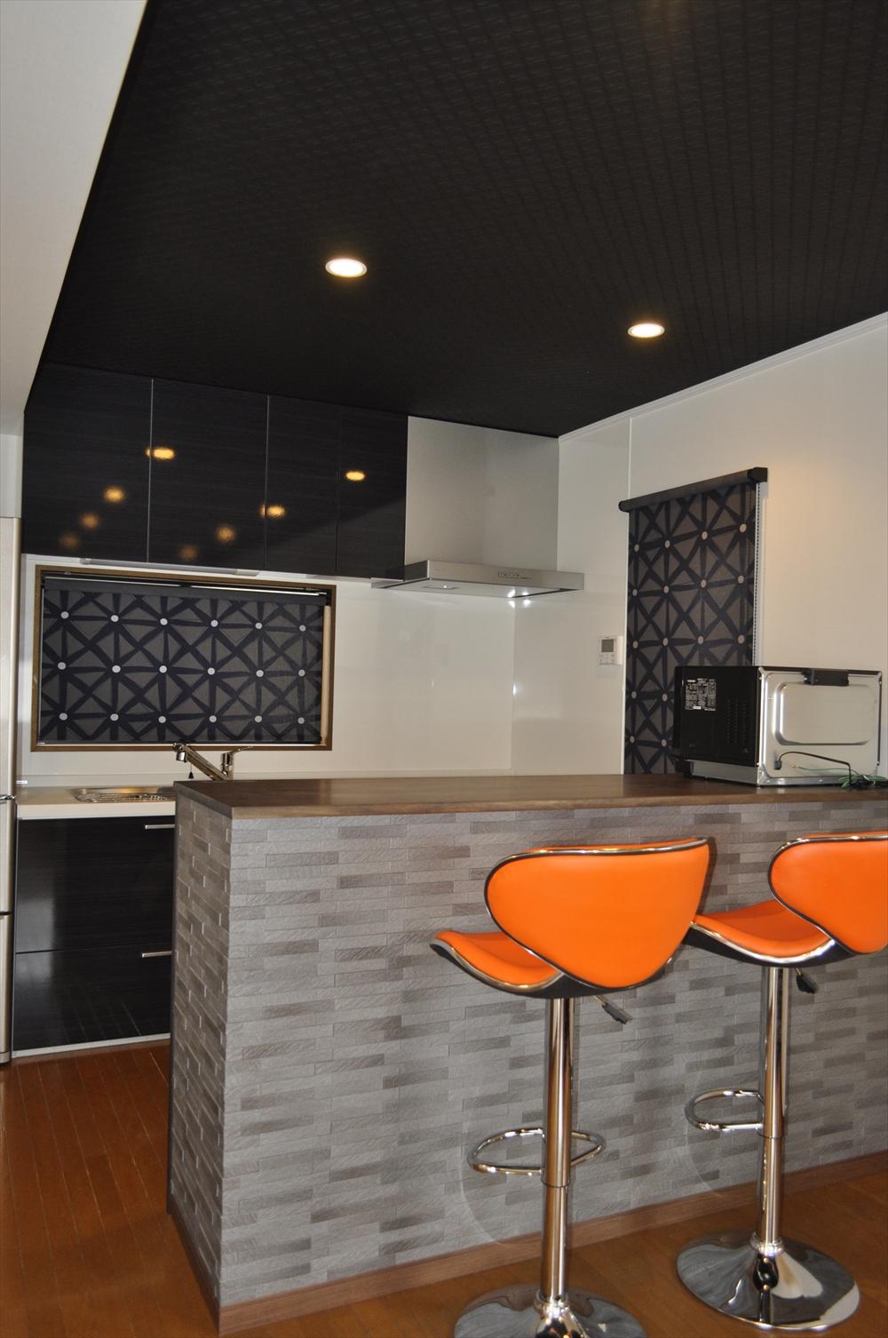 ブラック×シルバーグレーのモダンなキッチン オレンジのチェア 匠工房